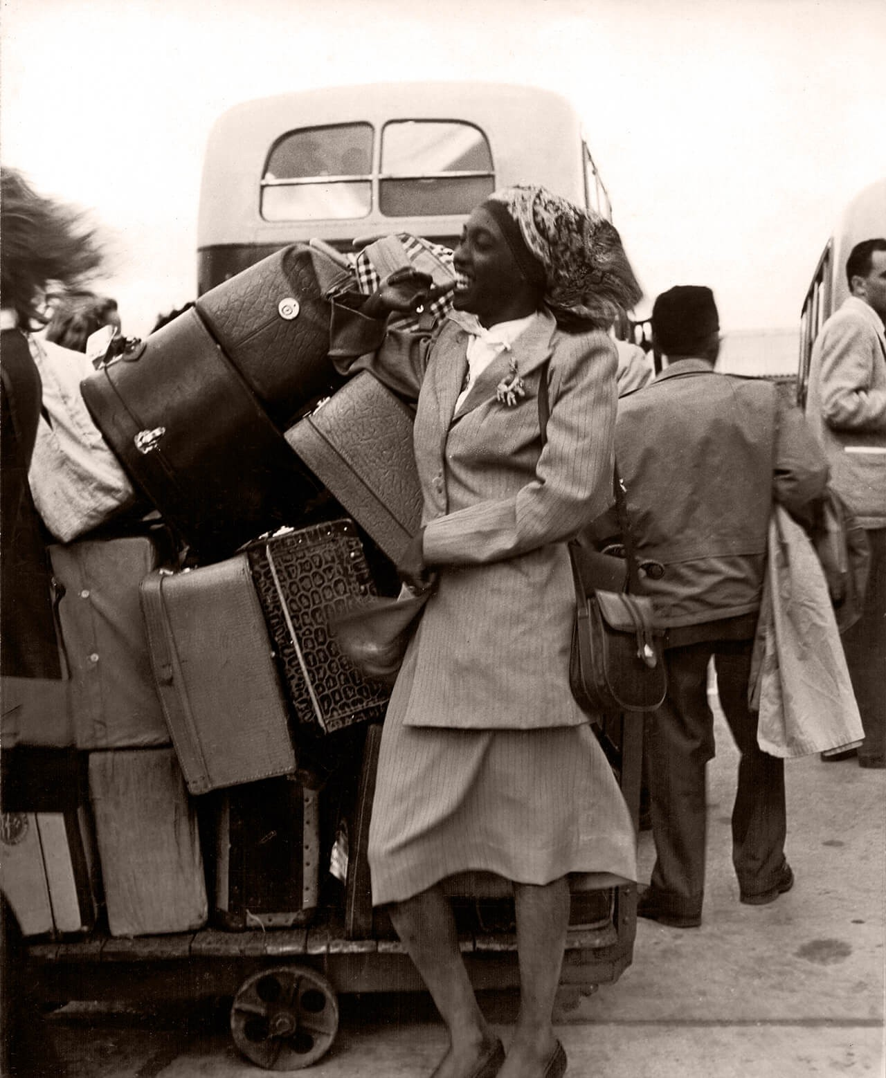 Melânia Luz, a primeira mulher negra a representar o Brasil em uma Olimpíada, sorri ao lado de malas na chegada a Londres, em 1948