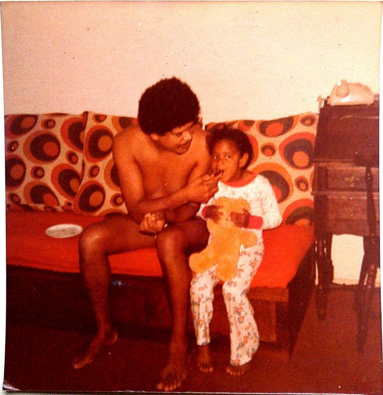 Em uma das tantas casas em que morou, Alessandra sentada ao lado do pai no sofá - Arquivo do pai