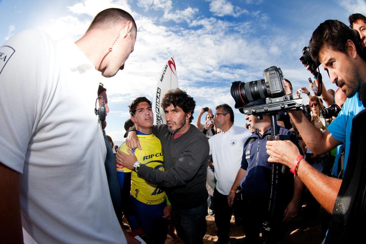 Abraçado com o padrasto e treinador, Charles, Medina aguarda a nota de Julian Wilson na final em Portugal 2012 - WSL / Kelly Cestari