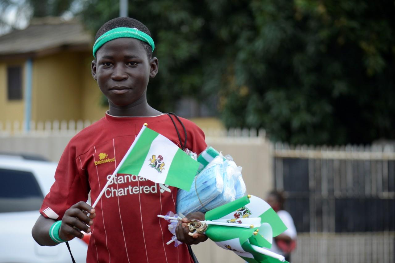 Menino nigeriano vende bandeiras durante a comemoração dos 60 anos da independência do país - Getty Images