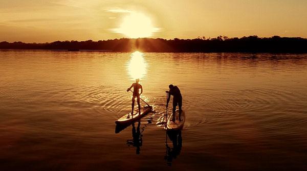 Dois praticantes de Stand Up Paddle em um rio ao por do sol