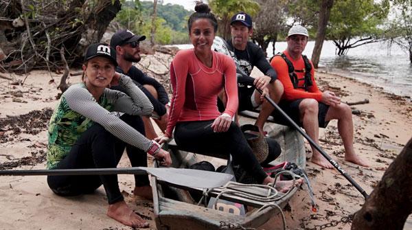 Clayton Conservani e Carol Barcellos tiram foto em cima de uma canoa com mais três pessoas na beira do rio