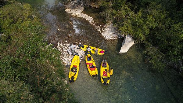 Foto aérea de pessoas descansando em canoas à beira do rio.