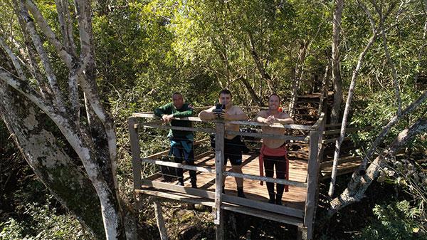 Foto de pessoas em uma ponte com uma floresta atrás.