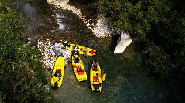 Foto de cima mostra pessoas dentro de canoas à margem de um rio