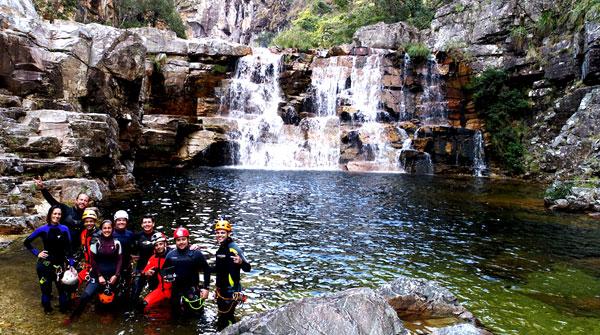 Foto dos apresentadores com um grupo de pessoas e uma cachoeira ao fundo