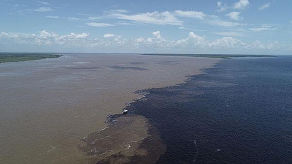 Foto de um extenso rio, com águas metade claras e metade escuras, com um pequeno barco ao meio
