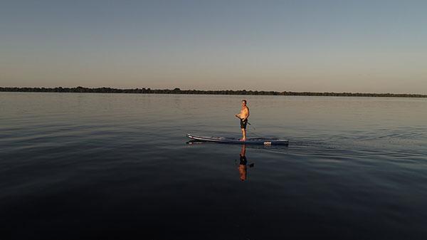 Foto do repórter Clayton em pé num Standup Paddle no Rio Negro