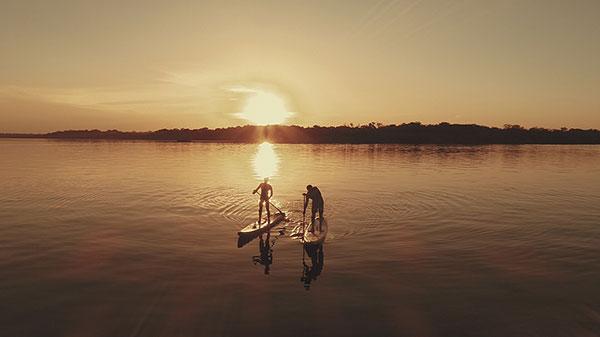 Foto dos repórteres Clayton e Carol fazendo standup no Rio Negro ao por do sol
