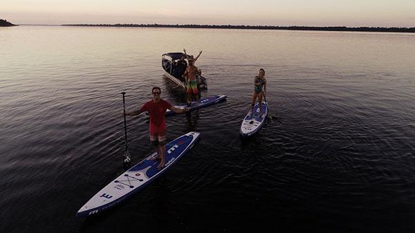 Foto de um grupo de quatro homens e uma mulher no Rio Negro. Dois dos homens estão dentro de um barco enquanto outros dois e a mulher estão posando em cima do standup paddle.