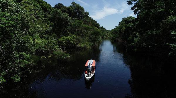 Foto de um barco navegando pelo Rio Negro, com vegetação em ambas as marges. Neste barco está um homem em com equipamento fotográfico.