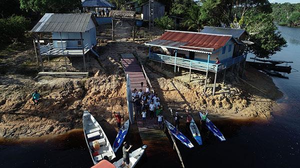 Foto aérea do cais de um povoado, com dois barco estacionado e quatro pranchas de standup. Na beira do cais há parte da população do vilarejo.