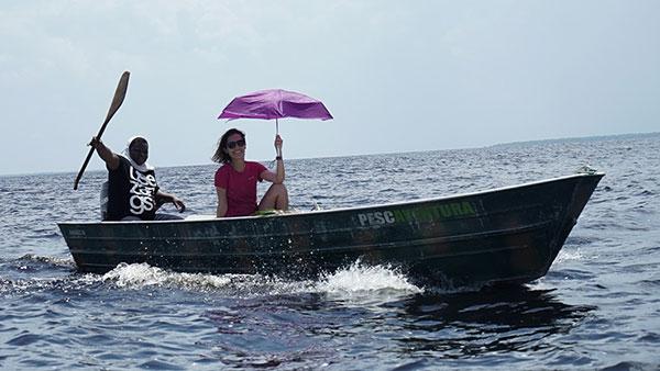 Foto de Carol Barcelos, carregando uma sombrinha aberta, navegando pelo Rio num barco de pesca.