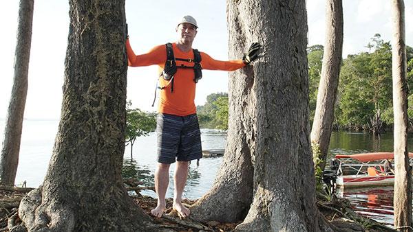 Clayton Conservani posando entre duas árvores nas margens do rio. CLayton veste blusa de manda comprida laranja, bermuda escura, boné e luvas.