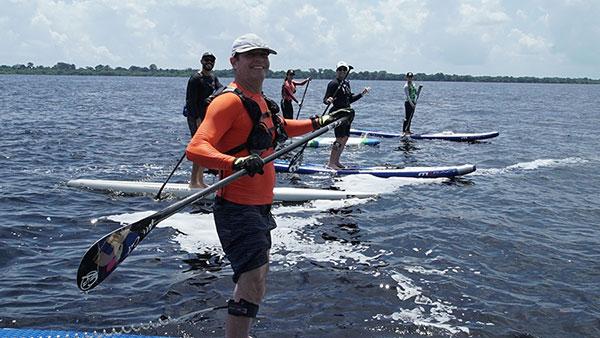 Cinco pessoas, incluindo Clayton e Carol, posando para a foto enquanto em pé standup no Rio Negro