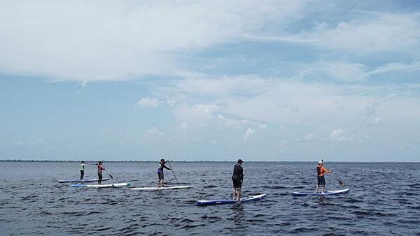 Foto do horizonte, com o Rio Negro na parte de baixo e cinco pessoas praticando standup paddle.