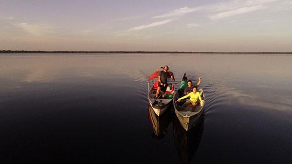 Foto do Rio Negro, ao por do sol, com cinco pessoas navegando em dois barcos de pesca.