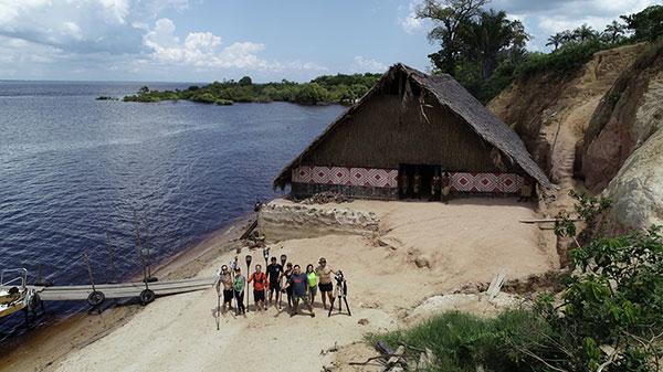 Foto aérea da margem de um vilarejo, perto de um cais improvisado. Ao fundo mostra vegetação. Perto de cais há uma oca. Perto do cais, há sete pessoas posando para a foto.