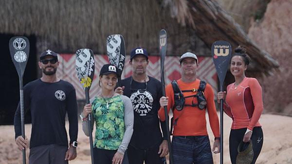 Foto de cinco pessoas, incluindo Clayton Conservani e Carol Barcelos, segurando seus remos, posando para a câmera. Todos estão vestidos com roupa adequada a pratica do esporte.