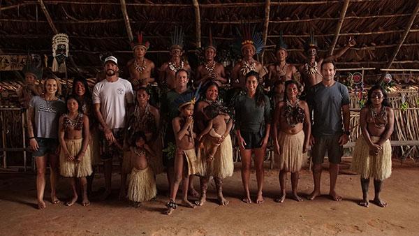 Foto de um grupo de pessoas, em sua maioria índios, dentro da oca.