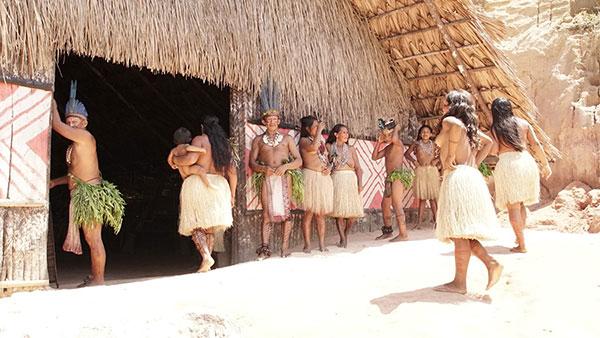 Foto da entrada da oca, com índios ao redor. Um índio escora-se na porta à esquerda, uma índia entra na oca segurando um bebê. Cinco jovens, 2 índios e 3 índias, estão em pé na parede externa da oca conversando. Duas índias jovens estão caminhando em direção a oca.