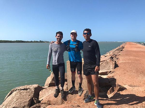 Conservani e dois homens em cima de um pedra com o mar atrás.