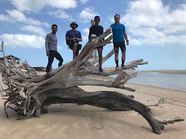 Conservai e mais três homens possam em cima de uma árvore caída na praia.