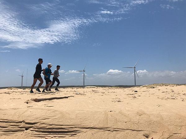 Apresentador Conservani e mais dois homens correndo na praia.