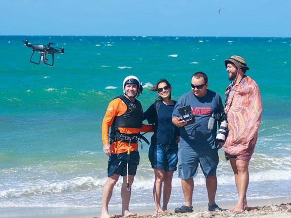 Apresentador Conservani junto com três pessoas na praia ao lado de um drone.