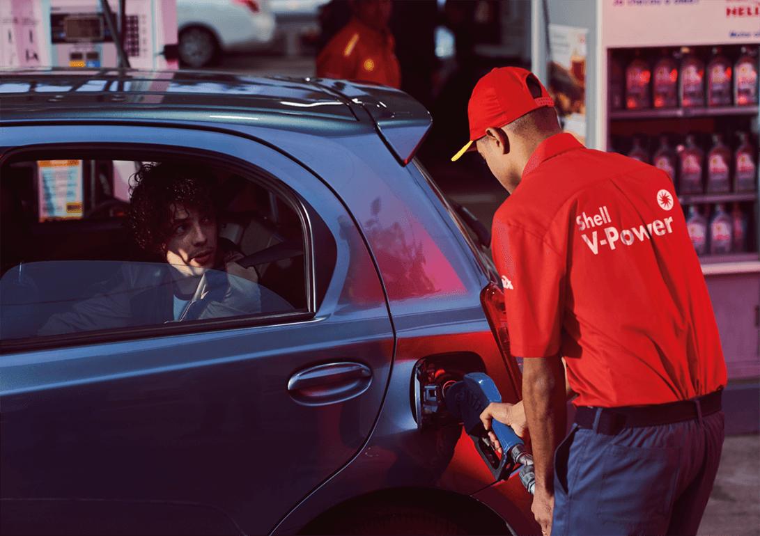Carro estacionado em um posto Shell e abastecendo.